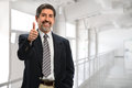 Businessman showing thumbs up senior hispanic inside office building Stock Photography