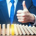 A businessman shows a thumbs up approval over a stopped process falling domino. Achieving success and completing a task. Solution Royalty Free Stock Photo
