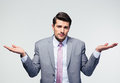 Businessman shrugging shoulders over gray background looking at camera Stock Photography