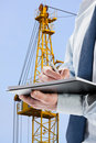 Businessman signing acceptance report contract construction crane in the background Royalty Free Stock Images