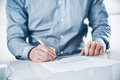 Businessman signing a contract or document sitting at desk with fountain pen close up of his hands Stock Image