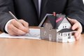 Businessman signs contract behind house architectu Royalty Free Stock Photography