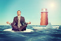 Businessman with sinking ship sitting in lotus position on small sand island in sea and looking up paper boat Stock Photography