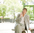 Businessman sitting on a bench in the financial district using his cell phones and having a conversation while sitting on a bench Royalty Free Stock Images