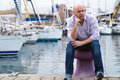 Businessman sitting by expensive sailing boats and yachts in a c Royalty Free Stock Photo