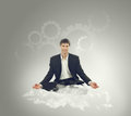 Businessman sitting in lotus position on a cloud Stock Photos