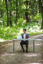 Businessman sitting at the office desk work at laptop computer and cup of coffee use mobile phone on road of green forest park. Bu Royalty Free Stock Photo