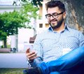 Businessman sitting on park bench with coffee using mobile phone. Royalty Free Stock Photo