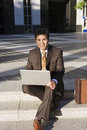 Businessman sitting on pavement steps, using laptop, smiling, front view, portrait Royalty Free Stock Photo