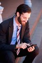 Businessman sitting and reading message on mobile phone portrait of a outside text Royalty Free Stock Photo