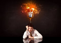 Businessman sitting under a blowing idea bulb Royalty Free Stock Photo