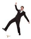 Businessman slipping on banana peel Royalty Free Stock Photo