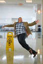 Businessman slipping on wet floor african american inside office building Royalty Free Stock Photography