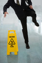 Businessman slipping on wet floor in front of caution sign in hallway Stock Photography