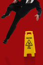 Businessman slipping on wet floor in front of caution sign over red background Stock Photo