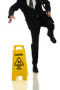 Businessman slipping on wet floor in front of caution sign over white background Royalty Free Stock Images