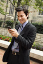 Businessman smiling at cell phone message. Royalty Free Stock Photo