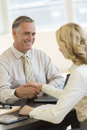 Businessman smiling while greeting colleague at desk mature female office Royalty Free Stock Photos