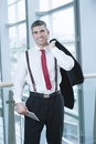 Businessman smiling and looking at camera with jacket over shoulder Royalty Free Stock Photo
