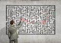 Businessman solving labyrinth problem back view image of young trying to find way out of maze Stock Photo