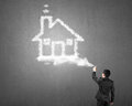 Businessman spraying house shape cloud paint with concrete wall Royalty Free Stock Photo