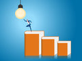 Businessman stand on stair step made of books to get light bulb idea. Creative idea and education concept.