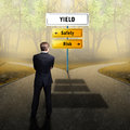 Businessman standing on a crossroad having the options Safety and Risk Royalty Free Stock Photo
