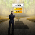 Businessman standing on a crossroad, having to choose the right path what to do with the words shares, sell and buy Royalty Free Stock Photo