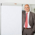 Businessman standing by flipchart in office portrait of confident mature Royalty Free Stock Image