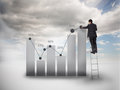 Businessman standing on a ladder drawing a chart with blue sky the background Stock Photo