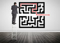 Businessman standing on a ladder drawing line through qr code in empty room Royalty Free Stock Images