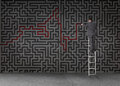 Businessman standing on a ladder and drawing a red line through black maze wall Royalty Free Stock Photos
