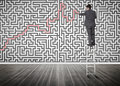 Businessman standing on a ladder solving maze puzzle in an empty room Stock Photo