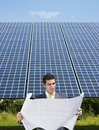 Businessman standing near solar panels Stock Images