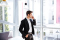 Businessman standing near the window and talking on cell phone Royalty Free Stock Photo