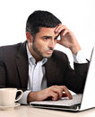 Businessman stressed and overworked close up of business man with computer looking worried with a cup of coffee on the desk Stock Photos