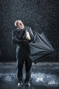 Businessman struggling to open umbrella in rain middle aged during sudden Stock Photos