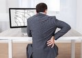 Businessman suffering from backache while sitting at desk Royalty Free Stock Photo