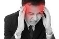 Businessman suffers from sickness severe headache with red alert accent Royalty Free Stock Photography