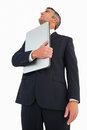 Businessman in suit holding his laptop proudly on white background Stock Image