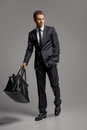 Businessman with suitcase. Full length of confident young busine Royalty Free Stock Photo