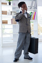 Businessman with suitcase talking on mobile phone Royalty Free Stock Photo