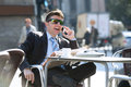 Businessman in sunglasses having breakfast coffee early morning reading newspaper news talking on mobile phone Royalty Free Stock Photo