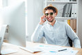 Businessman in sunglasses talking on cell phone in office