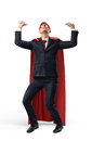 A businessman in superhero costume over his suit trying to hold a heavy invisible heavy object from above.