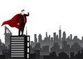 Businessman superhero standing over city background.