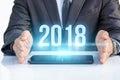 Businessman on tablet shows 2018 .
