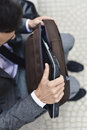 Businessman taking a laptop out of a briefcase Royalty Free Stock Photo