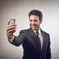 Businessman taking a picture of himself with smarphone Stock Image