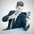 Businessman taking a selfie young man sitting at his desk and with his smart phone Stock Photo